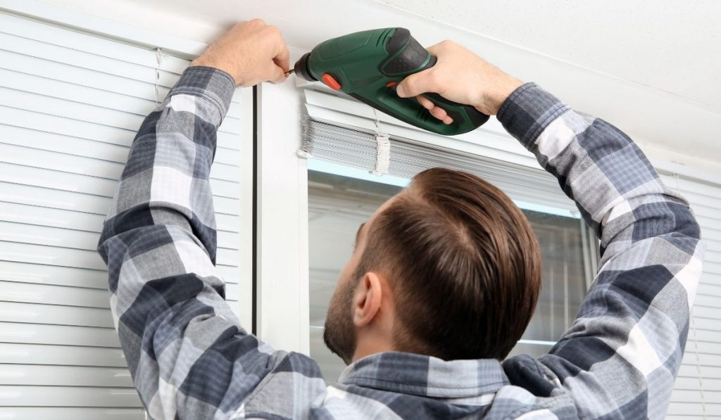 man in checkered shirt installing window shades