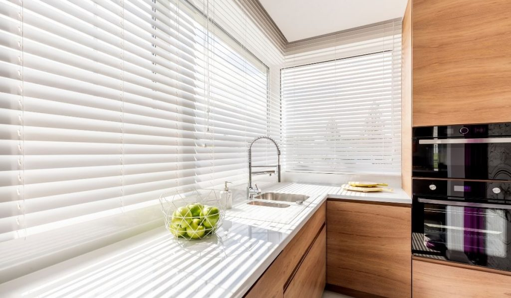 bright kitchen room at an apartment with white window blinds