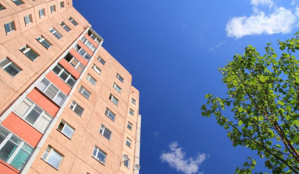 facade of skyscraper with apartments with blue sky and a tree