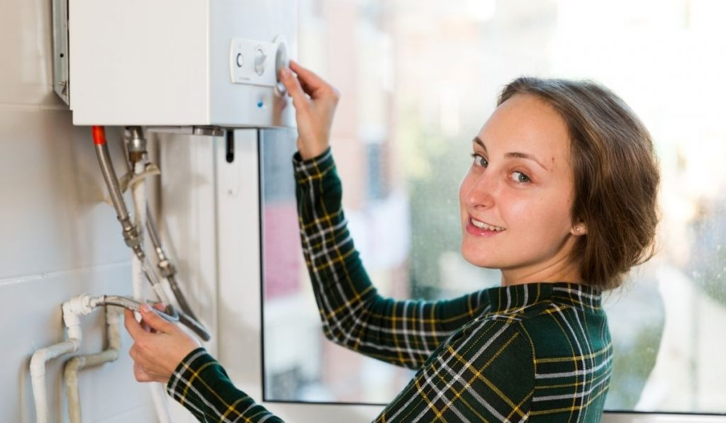 girl adjusting the water heater in her apartment