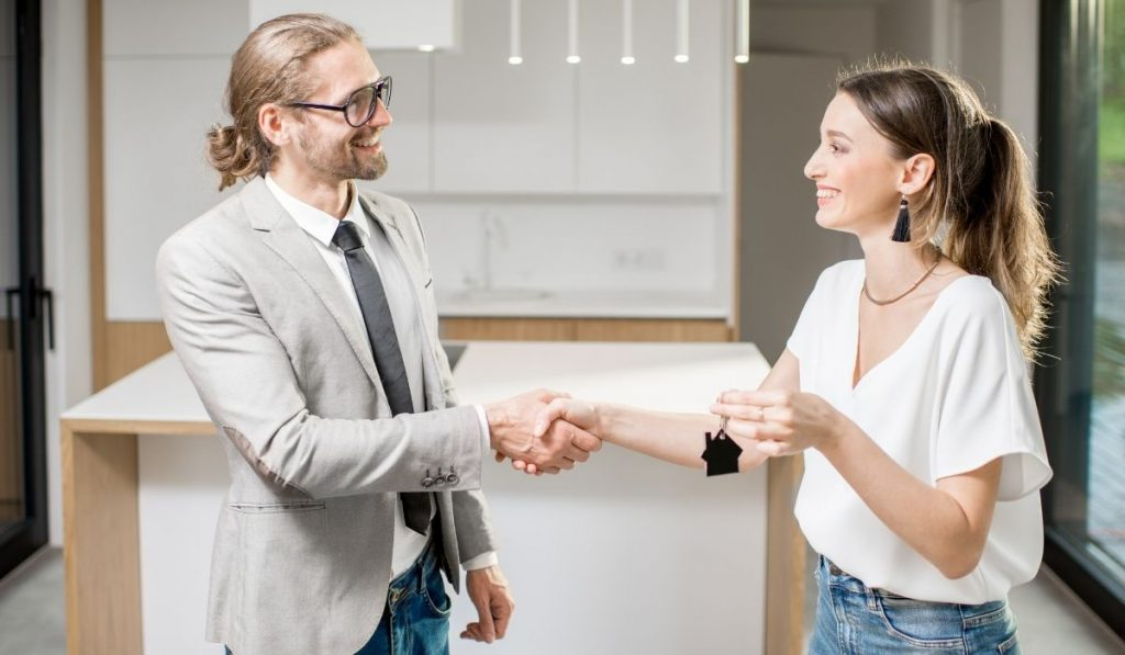 happy young woman receiving the key to her new apartment