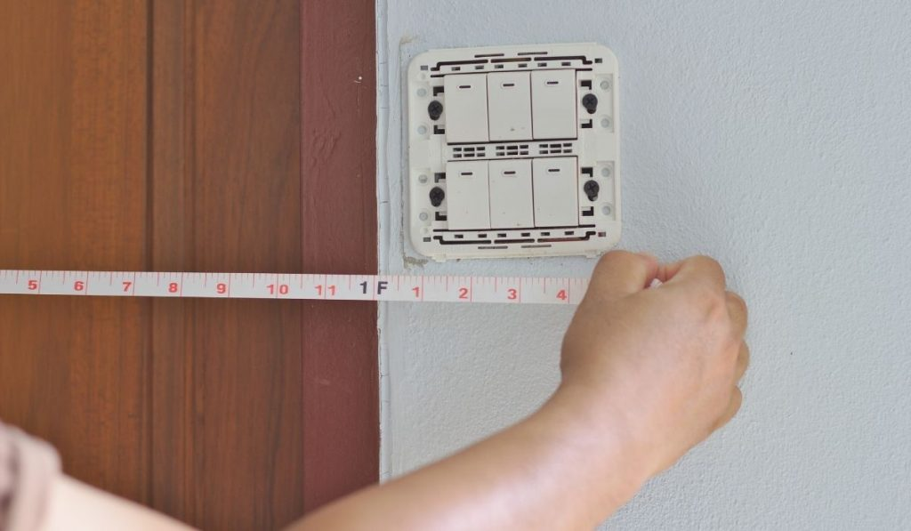 man using a measuring tape to measure the distance from the switch panel to an unknown point outside the photo