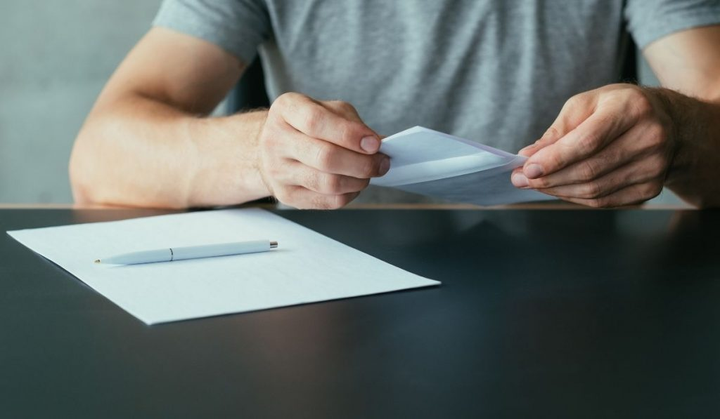 man writing an application for an apartment lease