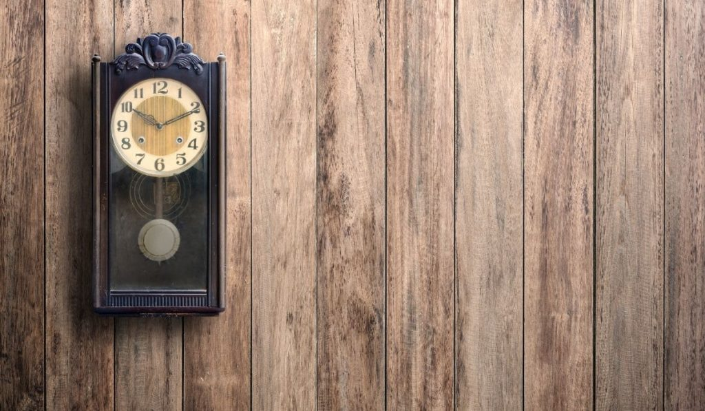 old clock hanging in a wooden wall