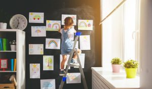 girl-on-a-ladder-hanging-her-drawings-on-the-wall