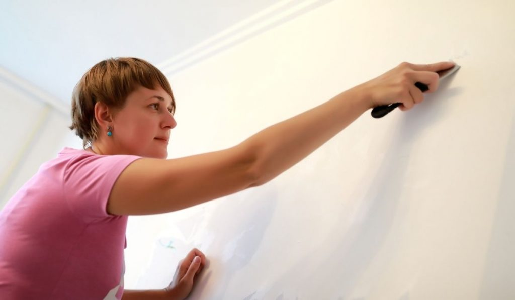 woman cleaning the wall