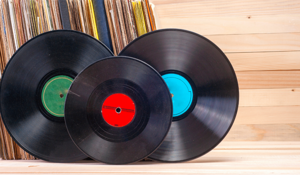 Three vinyl records leaning on its case with wooden background.