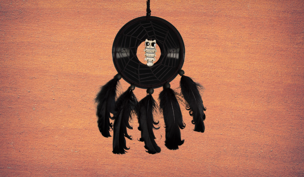 Vinyl records converted into a dream catcher on an orange wall.