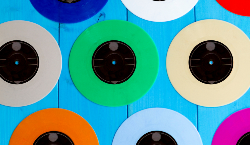 Colorful vinyl records mounted on a blue wall.